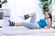 Young girl doing exercising with legs weights