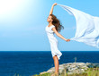 Freedom Concept. Girl with White Scarf standing on the Rock