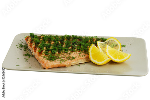 Grilled salmon fish fillet with dill and lemon on grey ceramic d