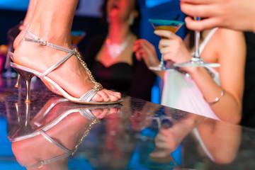 Frau in einem Club oder Bar tanzt auf dem Tisch