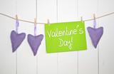 3 Stoffherzen auf Leine mit Valentinstag vor Holzwand