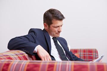 Geschäftsmann mit Tablet Computer auf Sofa