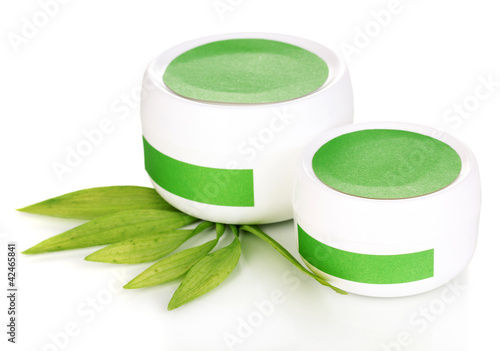Jars of cream with green leaves isolated on white