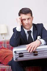 Manager mit Koffer im Hotelzimmer