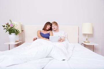 Paar im Bett mit Tablet Computer