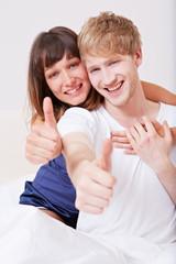 Junges Paar hält Daumen hoch