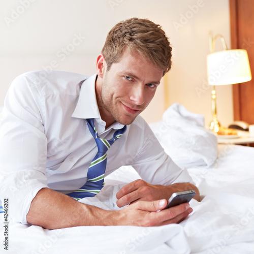 Mann liegt mit Smartphone im Bett