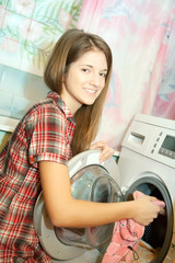 Teenager girl loading the washing machine