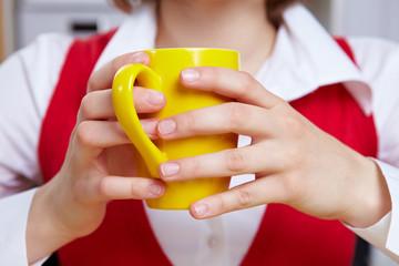 Hände halten Tasse im Büro