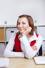 Managerin sitzt lächelnd am Schreibtisch