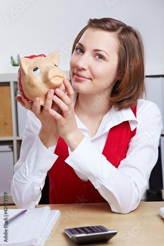 Frau mit Sparschwein am Schreibtisch