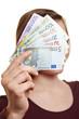 Frau hält Geldscheine vor Gesicht