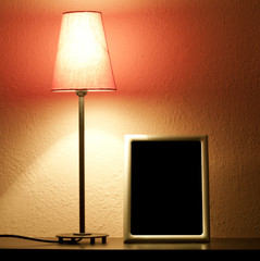 Lamp and empty frame on the shelf in night abstract concept