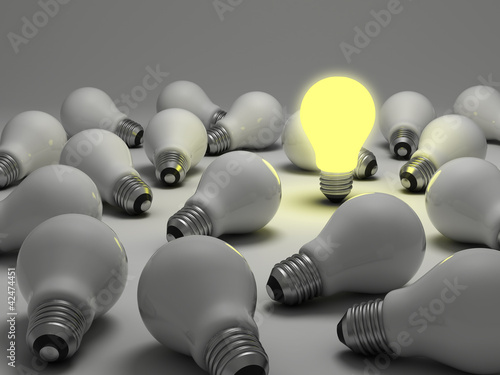 Lit light bulb amongs unlit incandescent bulbs
