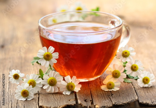 cup of tea and chamomile flowers on a wooden table
