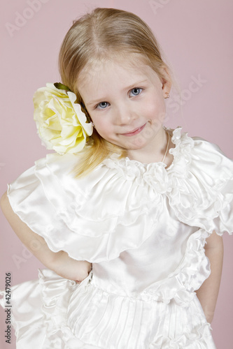 Portrait of the child in a white dress with a flower