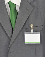 Male gray business suit, green tie and name badge