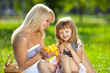 Beautiful smiling young mother and little daughter at a picnic
