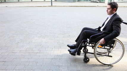 Business man in wheelchair talking into smartphone