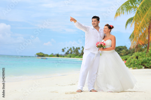 Bride and groom embracing on beach, Kuredu island, Maldives