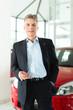 Älterer Mann oder Verkäufer mit Auto im Autohaus