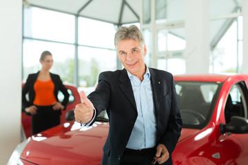 Älterer Verkäufer mit Auto und Frau im Autohaus