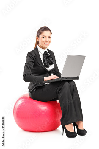 A smiling woman sitting on a pilates ball and working on a noteb