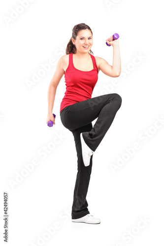 Full length portrait of a smiling teenager lifting up a dumbbell