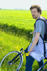Man cyclist relaxing against the background of green fields in s
