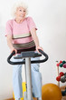 Happy Senior Woman Exercising On Bike