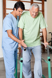 Therapist Assisting Senior Man To Walk With The Support Of Bars