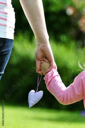 Mutter hält Kinderhand mit Herz
