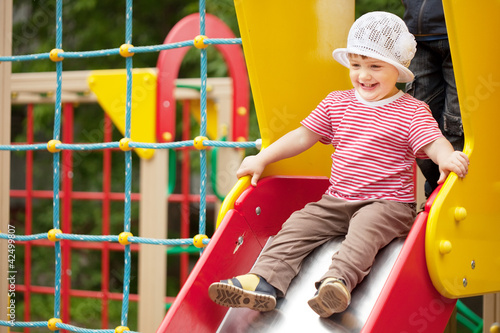 Happy two-year child on slide