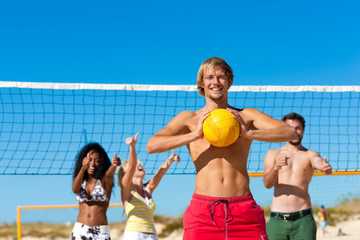 Friends playing beach volleyball