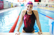 Portrait of a beautiful girl in a red cap at the swimming pool