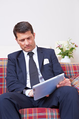 Manager arbeitet an Tablet Computer auf Sofa