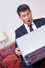 Überraschter Geschäftsmann schaut in Koffer