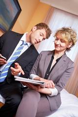 Geschäftsleute im Hotelzimmer lesen Zeitung