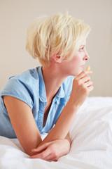 Frau isst Karotte im Bett