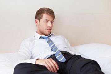 Müder Geschäftsmann liegt im Bett
