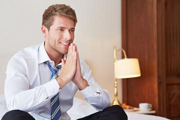 Geschäftsmann faltet Hände zum Gebet