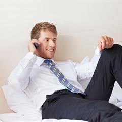 Geschäftsmann telefoniert im Bett