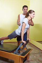 Trainer hilft Frau im Fitnesscenter