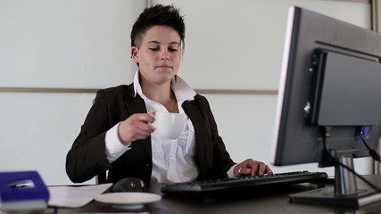 Young punk businesswoman drinking coffee in the office