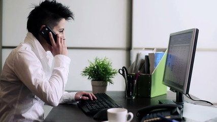 Punk businesswoman working on computer and talking on telephone