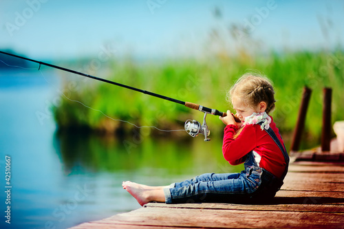 little girl fishing from wooden dock on lake