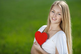 Young woman holding heart shape, on grass background