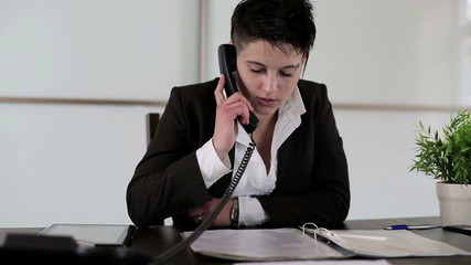 Young punk businesswoman talking on telephone in the office