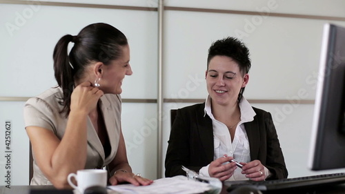 Two businesswomen gossiping and drinking coffee in the office