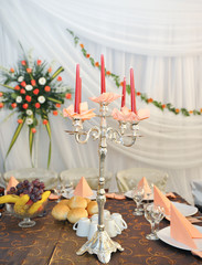 candlestick with candles and floral arrangements on wedding